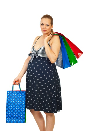 Beauty pregnant woman at shopping holding colorful bags isolated on white background photo