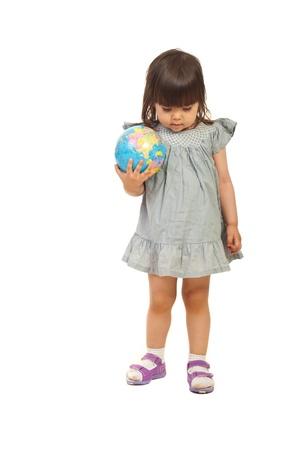 naar beneden kijken: Weinig kind meisje twee jaar oud bedrijf wereldbol en te mediteren op een witte achtergrond