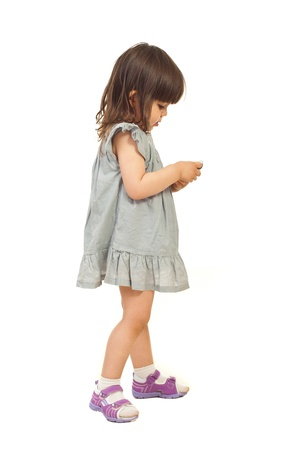 see side: Little girl standing in profile and sending message on phone mobile isolated on white background