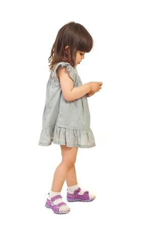 jolie petite fille: Petite fille debout dans le profil et l'envoi de message sur t�l�phone mobile isol� sur fond blanc Banque d'images
