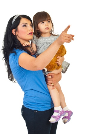 Mother holding toddler daughter and pointing away  isolated on white  background photo