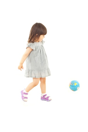 run down: Toddler girl in action playing soccer with world globe isolated on white background