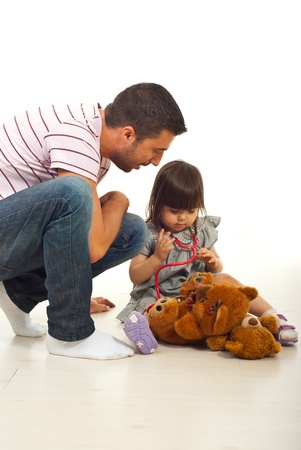 Father teaching his little daughter to use stethoscope  in their home photo