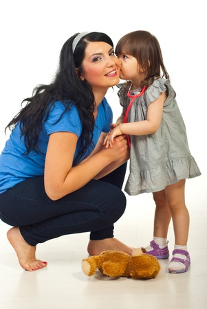Little daughter telling a secret or kissing mother in their home photo