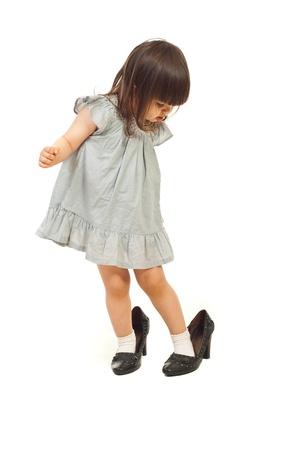 jolie petite fille: Fille de tout-petits grosses chaussures et regarde avec visage attentif isol�e sur fond blanc