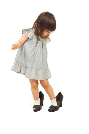 pie bebe: Ni�a ni�o zapatos grandes y mirando hacia abajo con cara atento aislada sobre fondo blanco