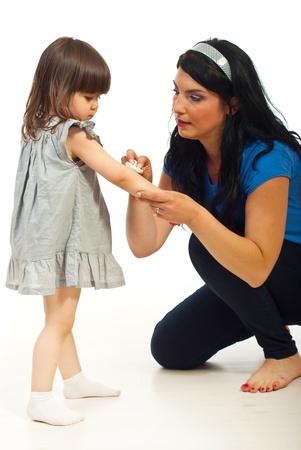 herida: Limpieza madre herida a su hija de ni�o y sentado en el piso sobre fondo blanco
