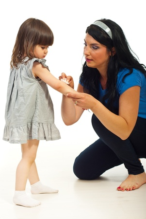 Mother cleaning wound to her toddler daughter  and  sitting on floor over white background Stock Photo