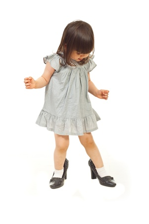 toddler walking: Little girl two years old wearing big shoes isolated on white background Stock Photo