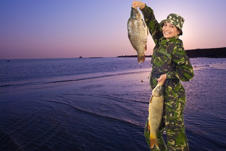 Happy fisherwoman at lake walking and holding two big carps in the morning at sunrise,copy space for text message in left part of image photo
