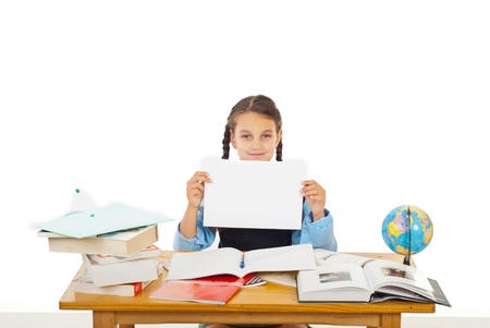 Student girl sitting at pupil with books showing black white paper isolated on white background photo