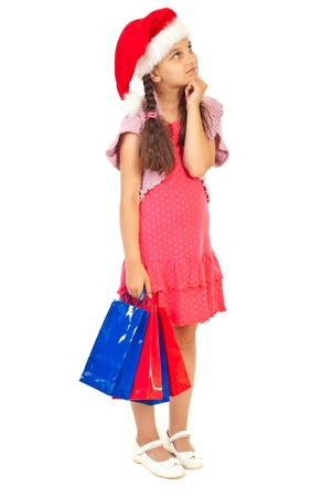 Little girl wearing Santa hat holding shopping bags and looking up to copy space isolated on white background photo