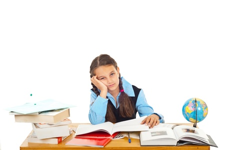 Bored schoolgirl with many books on table tired of studying against white background photo