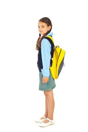 Toute la longueur du jeune fille étudiant permanent dans le profil de semi et regardant la caméra isolée sur fond blanc