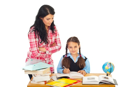 Teacher woman verify schoolgirl homework in a classroom against white background photo