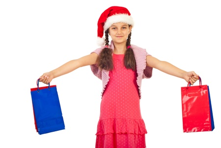 wearing santa hat: Happy girl wearing Santa hat and holding Chriostmas shopping bags isolated on white background Stock Photo