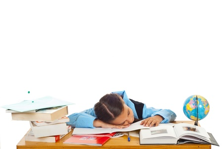 Tired schoolgirl sleeping on books at pupil isolated onw hite background photo