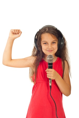 ni�o cantando: Chica alegre con auriculares cantando en micr�fono aislada sobre fondo blanco
