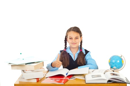 Schoolgirl sitting at pupil in classromm and giving thumb up isolated on white background photo