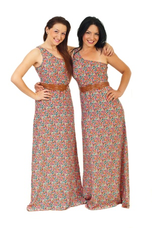 adult sisters: Happy beautiful sisters wearing same dress and standing in embrace isolated on white background