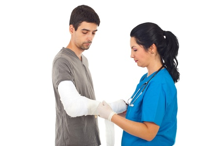 Doctor woman applying bandage to injured patient man hand isolated on white background photo