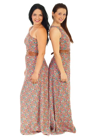Beautiful women wearing same dress and standing back to back isolated on white background photo