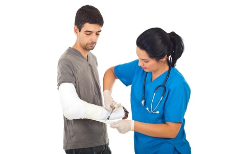 broken arm: Doctor woman bandage and using scissors to injured hand man isolated onw hite background