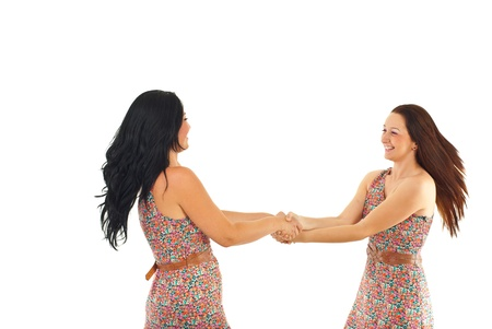 Two happy women holding hands and twirl together isolated on white background Stock Photo - 9886124