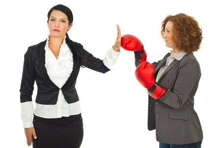 Serious business woman give stop hand to her colleague woman with boxing glove isolated on white background Stock Photo