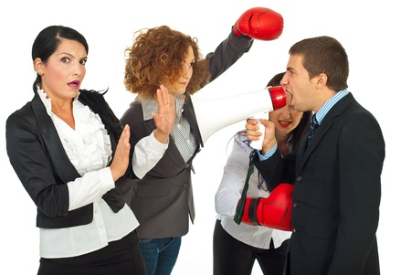 business disagreement: Furious manager man shouting into megaphone to scared employeed woman and her colleagues women trying to defend with boxing gloves and hit manager isolated on white background Stock Photo