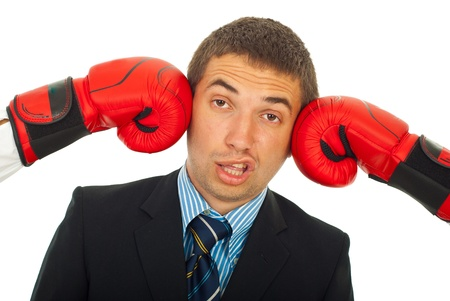Business man being kicked by two boxing gloves and making a face isolated on white background photo