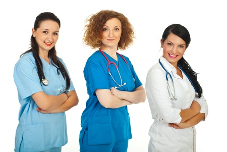 Friendly team of three doctor women in different uniforms standing in semi profile in a row with hands crossed isolated on white background photo