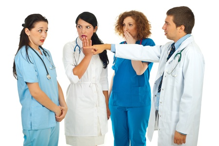 Hospital manager accusing  doctor woman and pointing and her colleagues doctors women being surprised and scared isolated on white background photo