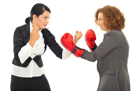 arguments: Competition  fight two business women ,one of them wearing boxing gloves isolated on white background