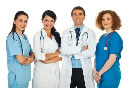 enfermeros: Feliz equipo de cuatro m�dicos de pie en una fila aislados sobre fondo blanco