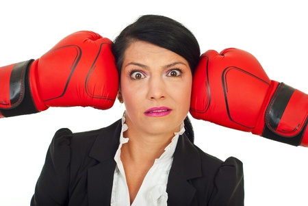 Stressed surprised executive woman with her head under boxing gloves pressure against white background Stock Photo