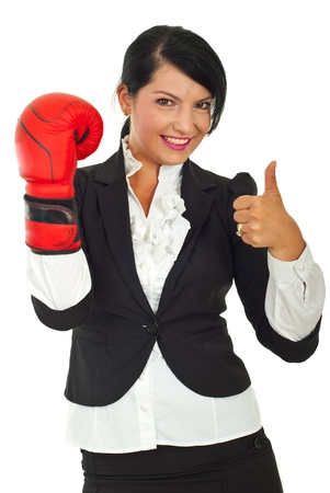 Successful business woman with boxing glove giving thumb up isolated on white background photo