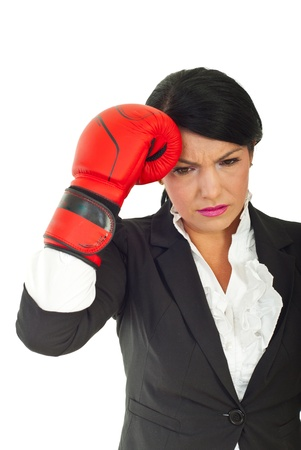 Unhappy business woman having problems and holding hand in boxing glove to head against white background Stock Photo - 10107752