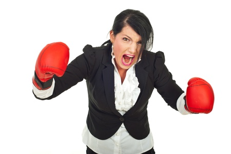 Extremely furious business woman in attack with boxing gloves against white background photo