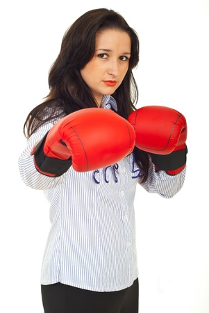 Young serious executive woman ina ttack and wearing boxing gloves against white background photo