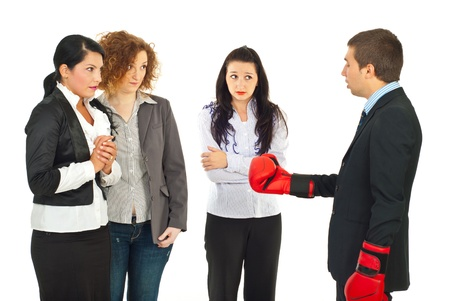 Manager wearing boxing gloves and having conflict with his employees women against white background photo