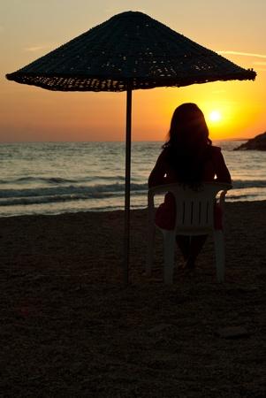 bewonderen: Vrouw zitten op de stoel onder de paraplu op het strand en genieten van de zonsondergang op zee Stockfoto