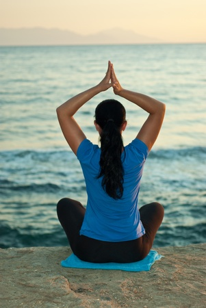 Back of woman doing yoga at sea in evening photo