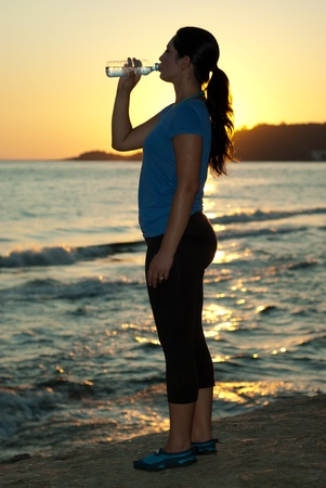 standing water: Fitness woman drinking water by sunset  at sea Stock Photo