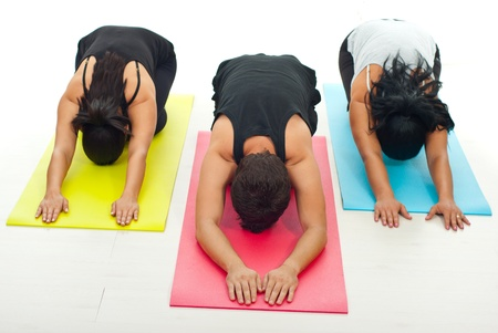 Group of three people doing yoga exercise on colorful gymnastics mats