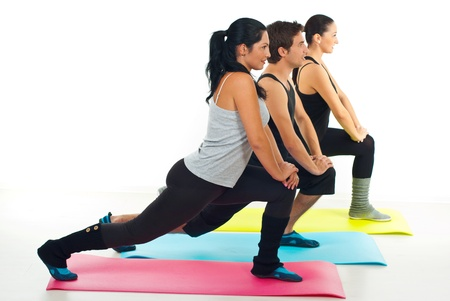 Fitness group of people doing exercises on colorful mats over white background