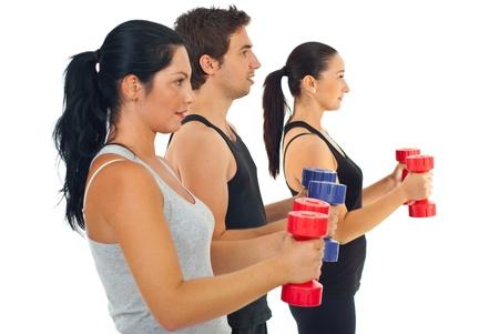 ejercicio aer�bico: Grupo de tres personas que hacen ejercicios de gimnasio con mancuerna contra blancos antecedentes Foto de archivo