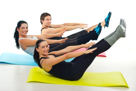Happy group of people stretching their hands and legs and sitting on colorful mats