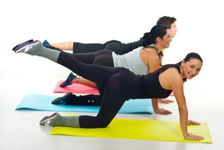 Grupo de tres personas flexionando sus piernas en un club de fitness