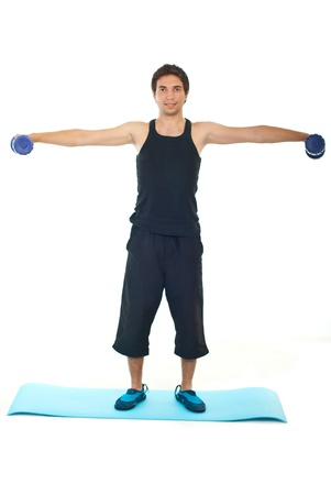 tracksuit: Fulllength of young man lifting barbell and standing on blue mat